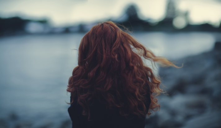 girl-with-curly-red-hair-in-the-wind-view-back-bokeh-photos